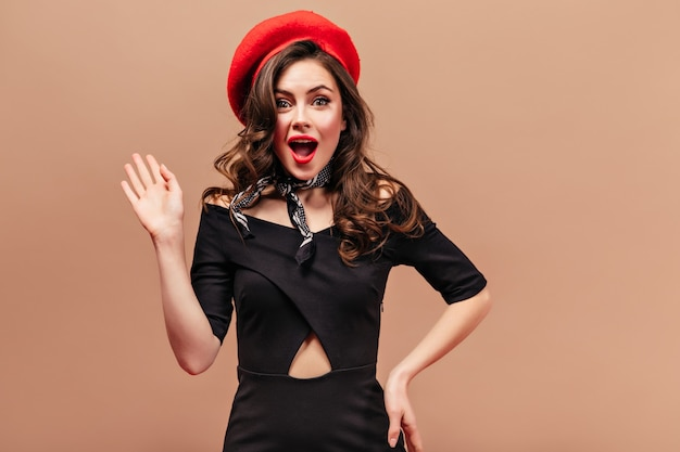 Portrait of green-eyed flirty lady dressed in dress, red beret and silk scarf. girl with red lips waving her hand.