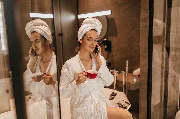 Ritratto di ragazza dagli occhi verdi in accappatoio dopo la procedura spa parlando al telefono. donna che beve il caffè in bagno.