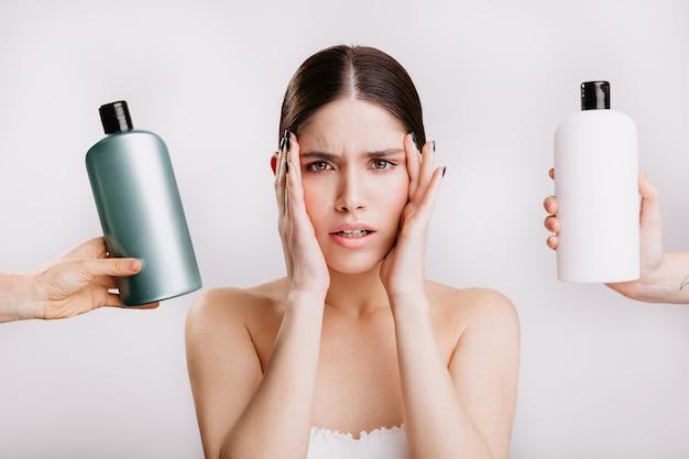 Ritratto di donna dagli occhi verdi senza trucco sulla parete isolata. la ragazza decide quale shampoo è meglio usare.