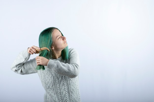 Ritratto di ragazza dai capelli verdi che pettina i suoi capelli sul grigio.