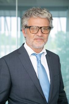 Ritratto di uomo d'affari dai capelli grigi in piedi