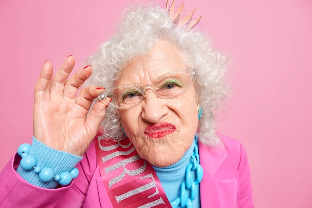 Portrait of grey haired wrinkled woman pouts lips looks attentively, keeps hand on rim of glasses dressed in fashionable clothes