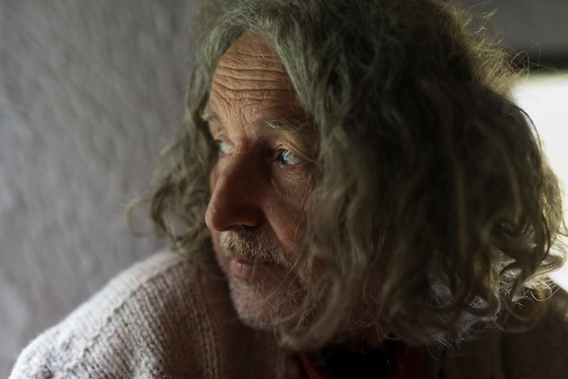 Portrait of grey long-haired serious senior man looking away.