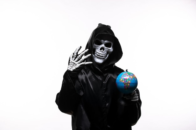 Portrait of grim reaper in black clothes with little globe on white