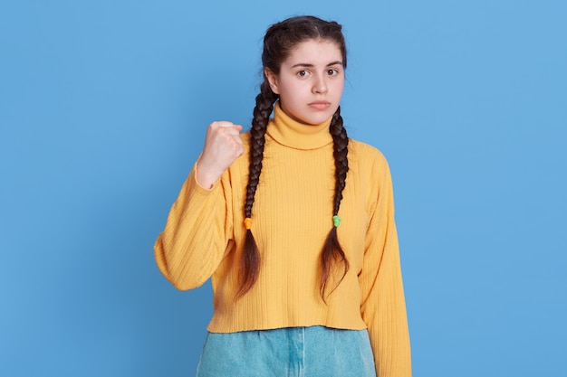 Portrait of grimacing sad girl model with pigtails, holding clasp hands in fists, wearing yellow jumper and jeans, posing isolated over blue vivid wall