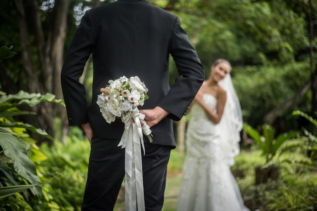 Portrait of a groom hiding a flowers bouquet behind his back to surprise to a bride.