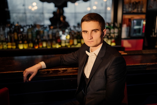 Portrait of a groom sitting on a chair by the bar. low key. close-up.