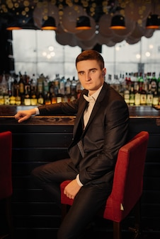 Portrait of a groom sitting on a chair by the bar. low key.