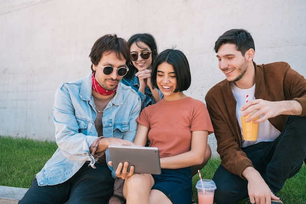 Portrait of group of friends having fun and using a digital tablet together while sitting outdoors. technology, lifestyle and friendship concept.