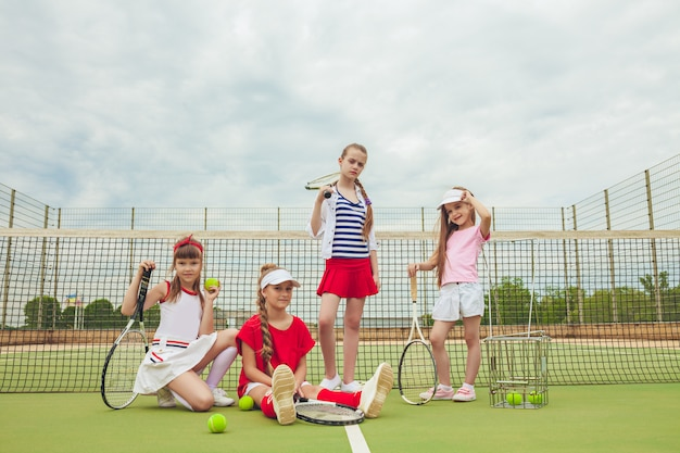 Portrait of group of girls as tennis players holding tennis racket against green grass of outdoor court