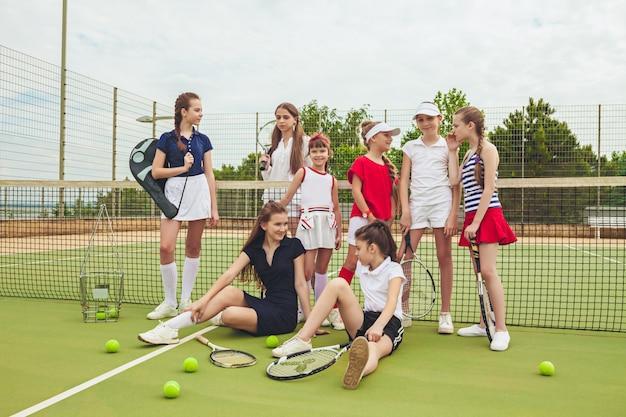 Ritratto del gruppo di ragazze come tennis che tengono le racchette di tennis contro l'erba verde della corte all'aperto.