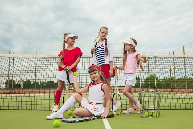 Portrait of group of girls as tennis players holding tennis rackets against green grass of outdoor court.
