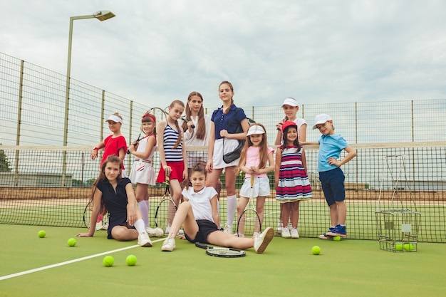 Portrait of group of girls and boy as tennis players holding tennis rackets against green grass of outdoor court.