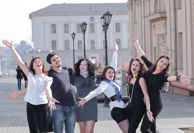 通りに立っている幸せな学生の肖像画グループ。