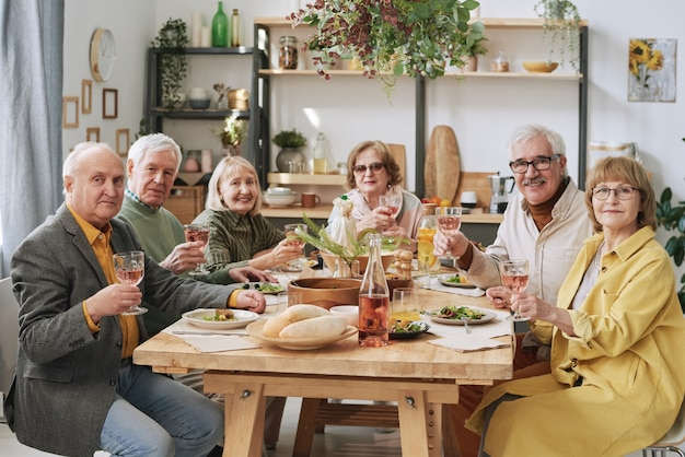 Portrait of group of old friends sitting at dining table with glasses of wine during dinner party