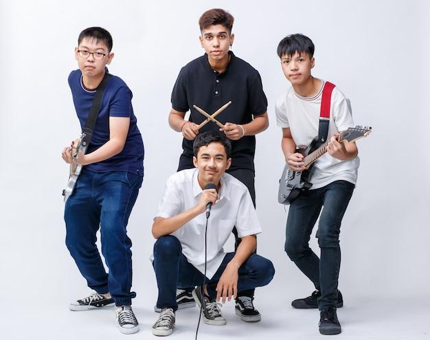 악기를 들고 흰색 배경으로 격리된 카메라를 바라보는 4명의 젊은 10대 소년 음악가의 초상화 그룹 샷. 어린 소년 기타리스트, 베이시스트, 보컬리스트 및 드러머의 그룹 샷