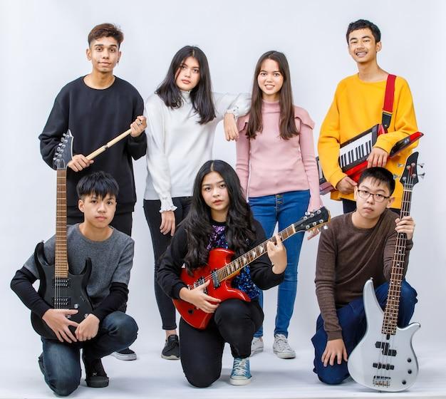 흰색 배경의 카메라를 바라보며 웃고 있는 7명의 10대 음악가의 초상화 그룹 샷. 기타리스트, 베이시스트, 보컬리스트, 드러머, 키보디스트의 그룹 샷. 음악가 친구의 개념