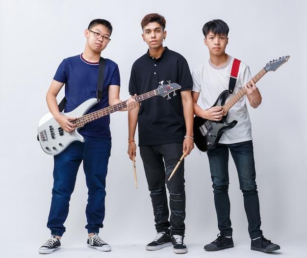 楽器を持って白い背景のカメラを見ている3人の10代のミュージシャンの肖像画のグループショット。少年ギタリスト、ベーシスト、ドラマーのグループショット。ミュージシャンの友達のコンセプト