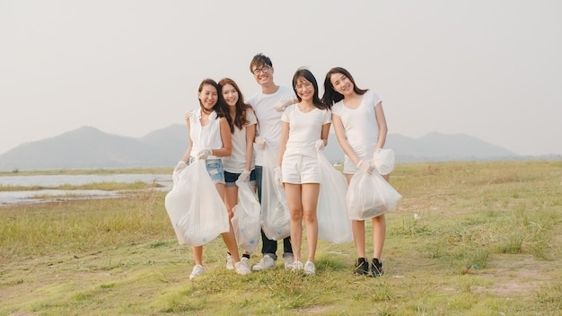 Portrait group of young multiethnical volunteers help to keep nature clean up looking at front and smile with white garbage bags on beach