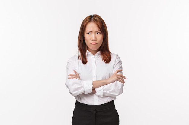 Portrait of grumpy and offended young asian woman, cross hands on chest defensive angry pose, look away as being insulted and outraged with someone being rude to her, white wall