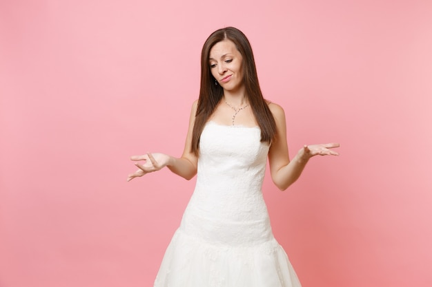 Portrait of guilty sad woman in beautiful lace white dress standing and spreading hands