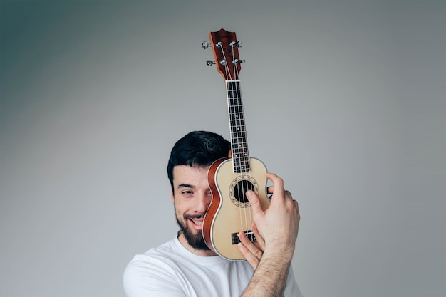 Portrait of guy cover face part with small ukulele