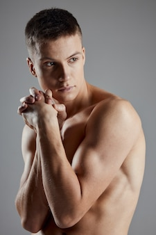 Portrait of a guy on a gray naked arm muscles bodybuilder fitness