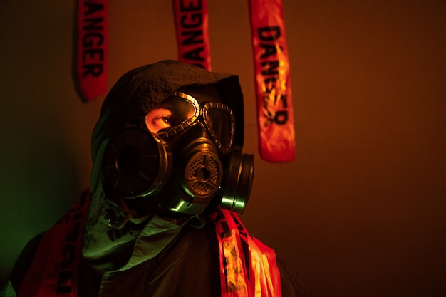Portrait of a guy in a green protective suit with a gas mask on his face and a hood on his head posing standing near a green wall with a large number of danger tapes closeupdanger