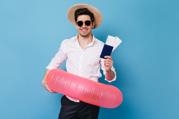 Ritratto di ragazzo in cappello e occhiali su uno spazio blu. uomo d'affari in camicia tiene i biglietti per il resto, passaporto e anello di gomma.