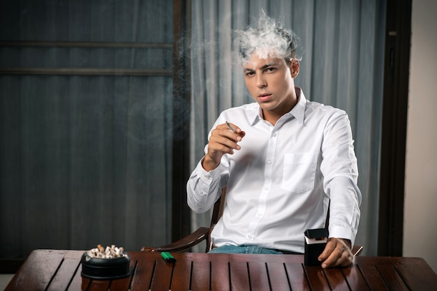 Portrait of a guy posing sitting at a table on which there is an ashtray full of cigarettes