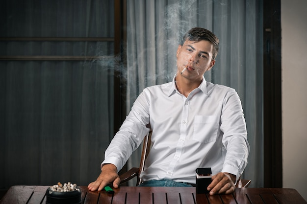 Portrait of a guy posing while sitting at a table on which stands an ashtray full of cigarettes