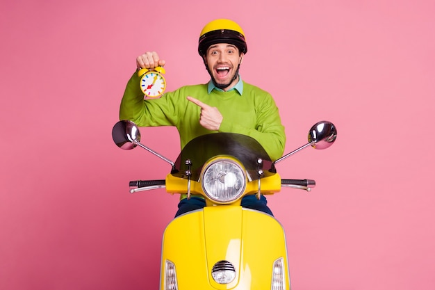 Portrait of guy sitting moped holding recommending funny alarm clock