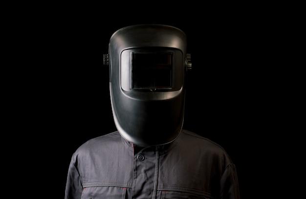 Portrait of a guy in a welding mask on a black