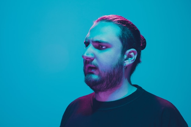 Portrait of a guy with colorful neon light on blue  wall. male model with calm and serious mood. facial expression, millenials lifestyle and look like. future, technologies.
