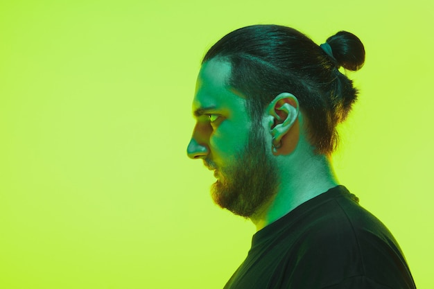 Portrait of a guy with colorful neon light on green studio background. male model with calm and serious mood.