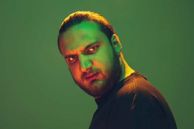 Portrait of a guy with colorful neon light on green  wall. male model with calm and serious mood. facial expression, millenials lifestyle and look like. future, technologies.