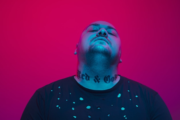 Portrait of a guy with colorful neon light on red background  cyberpunk concept