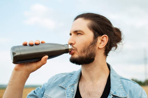 Portrait of guy with ponytail hairstyle drinking water from thermo bottle.