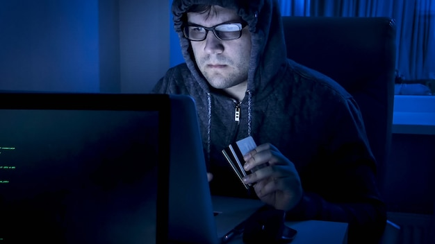 Portrait of hacker holding credit cards working on computer at night