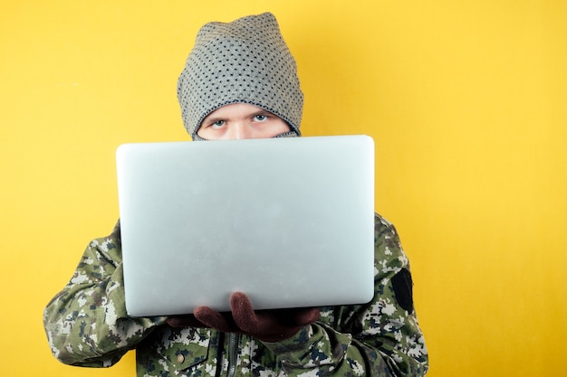 Portrait of a hacker man terroris in a camouflage and a mask is looking at the laptop