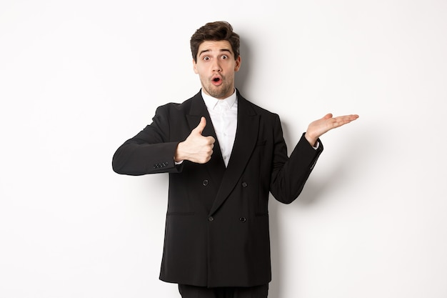 Portrait of hadnsome bearded man in formal suit, showing thumb-up and holding product in hand over white copy space, recommending product, standing over white background
