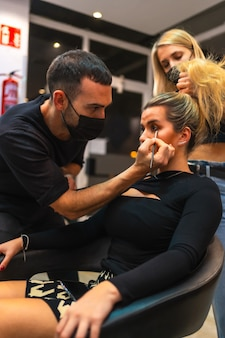 Portrait of a hairdresser and makeup artist in medical masks doing their job new normal