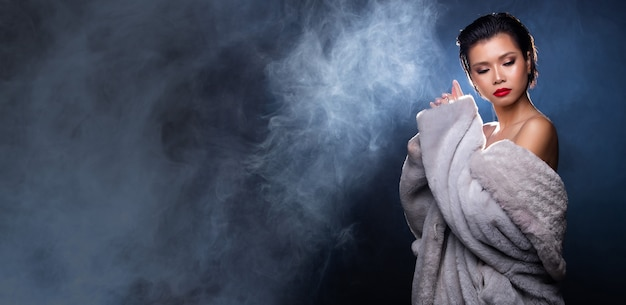 Портрет половина тела азиатской красивой женщины в сером меховом платье высокой моды на фоне дымового тумана с подсветкой сзади, скопируйте космический баннер