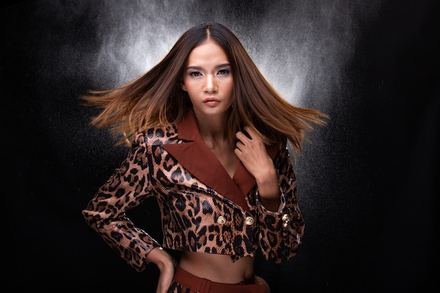 Portrait half body of young asian woman tan skin high fashion wears snake skin pattern dress, spin head throw hair. studio lighting black background isolated copy space, backlit light with effect fog