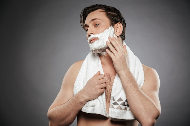 Portrait of half naked adult guy putting shaving foam on face with towel on his neck isolated over gray wall