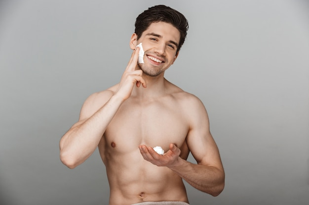 Portrait of half naked charming young man applying facial cream