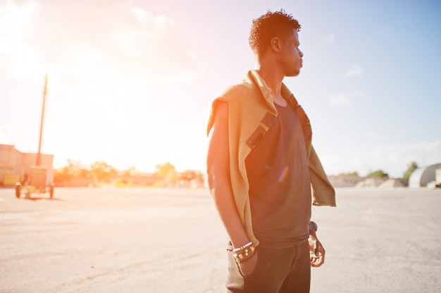 Portrait of a handsome african american guy in black muscle shirt posing in industrial zone.