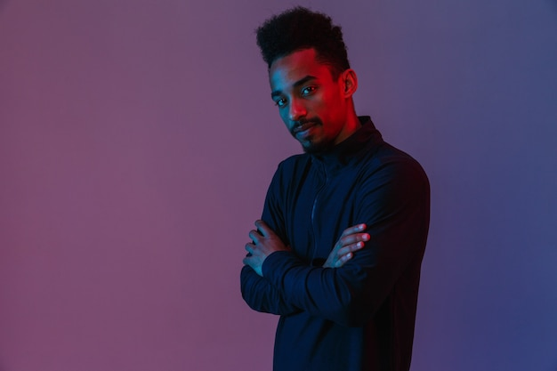Portrait of handsome african american man in sportswear posingwith his arms crossed isolated over violet wall