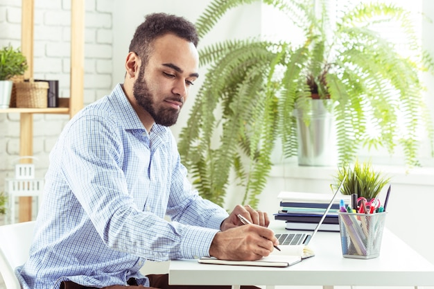 Portrait of handsome african black young business man working on laptop at office