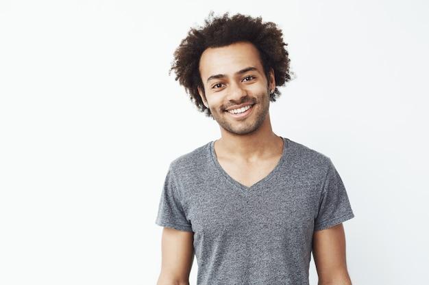 Ritratto di bel ragazzo africano sorridente sul muro bianco. studente fiducioso o giovane uomo d'affari.